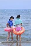 有一个浮游物的两个年轻中国女孩在蓝色海 烟台,中国 免版税库存图片