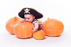 有一个海盗帽子的逗人喜爱的婴孩在他的说谎在他的胃的头  库存照片