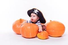 有一个海盗帽子的逗人喜爱的婴孩在他的说谎在他的胃的头  免版税库存照片