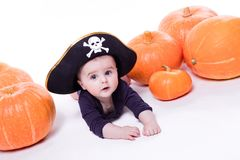 有一个海盗帽子的逗人喜爱的婴孩在他的说谎在他的胃的头  免版税图库摄影