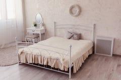 有一个混凝土墙、床和一张女性桌的卧室 库存图片