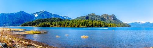 有一个渔船的全景在有雪的Pitt湖在海岸山脉加盖了金黄耳朵和其他山的峰顶 免版税库存图片