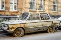 有一个漏,生锈和腐烂的身体的老被放弃的葡萄酒减速火箭的汽车与残破的光和窗口在泄了气的轮胎是一个在t中 免版税库存照片