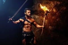 有一个火炬的无所畏惧的年轻肌肉战士在黑暗 免版税图库摄影