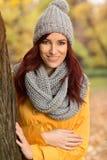 有一个灰色围巾和盖帽的微笑的妇女 免版税图库摄影