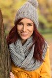 有一个灰色围巾和盖帽的愉快的女孩 图库摄影