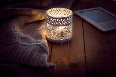 有一个灼烧的蜡烛和ebook读者的被编织的毛线衣 库存图片