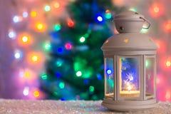 有一个灼烧的蜡烛的圣诞节白色灯笼在圣诞树的背景,诗歌选, bokeh光  免版税库存照片