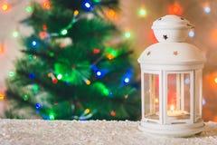 有一个灼烧的蜡烛的圣诞节白色灯笼在圣诞树的背景,诗歌选, bokeh光  免版税图库摄影