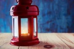 有一个灼烧的蜡烛的灯笼里面在黑暗的一张木桌上 图库摄影