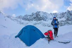 有一个热水瓶的妇女在营地的蓝色帐篷在山 免版税库存照片