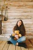 有一个熊玩具的行家女孩在木背景 免版税库存图片