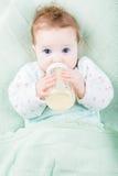 有一个牛奶瓶的美丽的矮小的婴孩在被编织的毯子下 库存照片