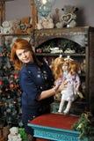 有一个玩偶的女孩在圣诞节 免版税库存照片