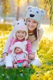 有一个玩偶的女孩在她的母亲和帽子 免版税库存图片