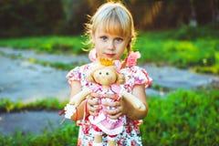 有一个玩偶的女孩在自然 库存图片