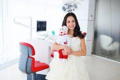 有一个玩偶的小女孩在诊所的背景 库存图片