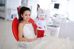 有一个玩偶的小女孩在诊所的背景 图库摄影