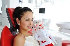 有一个玩偶的小女孩在诊所的背景 免版税库存图片