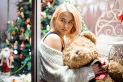有一个玩具熊的愉快的女孩在一棵装饰的圣诞树附近 新年度 库存图片