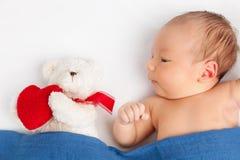 有一个玩具熊的逗人喜爱的新出生的婴孩在毯子下 免版税图库摄影
