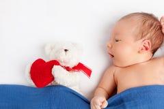 有一个玩具熊的逗人喜爱的新出生的婴孩在毯子下 免版税库存照片