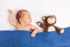 有一个玩具熊的逗人喜爱的新出生的婴孩在毯子下 免版税库存图片