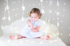有一个玩具的可爱的小孩女孩在圣诞灯之间的一张白色床上 免版税库存图片