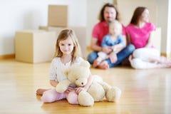 有一个玩具的愉快的小女孩在她新的家 库存照片