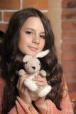 有一个玩具的美丽的青少年的女孩在手上 图库摄影