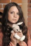 有一个玩具的美丽的青少年的女孩在手上 免版税库存照片