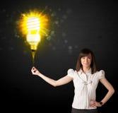 有一个环境友好的电灯泡的女实业家 免版税库存照片