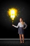 有一个环境友好的电灯泡的女实业家 免版税库存图片
