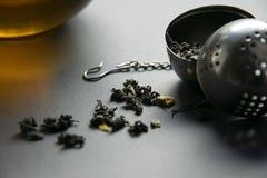 有一个玻璃杯子的滤茶器在灰色背景 免版税库存照片
