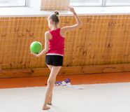 有一个球的女孩在一位专业体操运动员 免版税库存照片