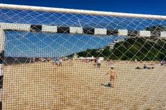 有一个球的男孩在海滩在橄榄球g的夏天 库存图片