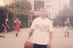 有一个球的蓝球运动员在他的手上 在街道上的一场篮球比赛每天 库存图片