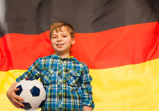 有一个球的年轻足球迷反对德国旗子 库存图片