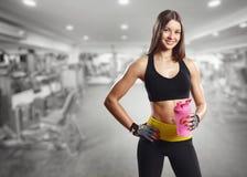 有一个瓶的一个女孩在健身房 免版税库存照片