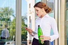 有一个瓶的企业夫人反对backgroun的净水 免版税图库摄影