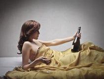 有一个瓶的可爱的妇女香槟 免版税图库摄影