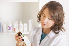有一个瓶的妇女药剂师医学 免版税库存图片