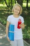 有一个瓶的愉快的女孩水和一张席子体育和瑜伽的在公园 免版税库存图片