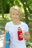 有一个瓶的愉快的白肤金发的女孩水和一张席子体育和瑜伽的在公园 健康生活方式 免版税图库摄影