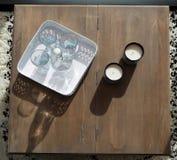 有一个瓶的盘子简单的水和玻璃在一张土气木桌上与蜡烛 库存照片