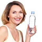 有一个瓶的美丽的年轻微笑的妇女水 免版税库存图片