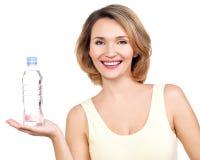 有一个瓶的美丽的年轻微笑的妇女wate。 图库摄影