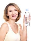 有一个瓶的美丽的年轻微笑的妇女wate。 免版税库存图片