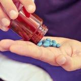 有一个瓶的年轻人蓝色药片 图库摄影