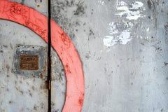 有一个生锈的号码锁的老灰色门 库存图片
